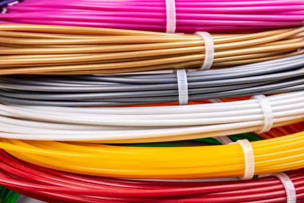 Bunch of colorful rolled cables. Closeup of plastic bright wires for 3D printer lying indoors, white studio background. Concept of children's entertainment and creativity.
