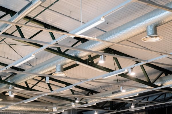 Factory building or warehouse building. Vast empty space with ventilation pipes and lights
