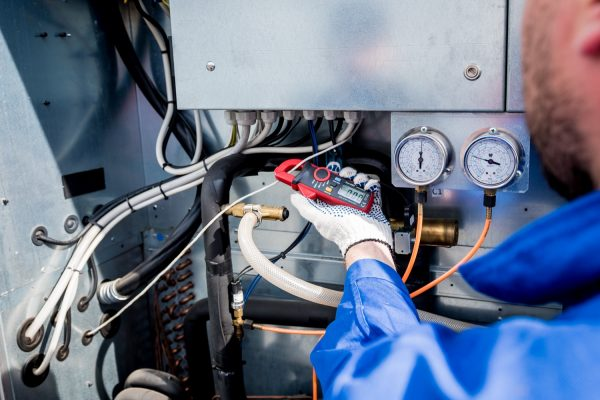 The technician checking power lines of the heat exchanger with current clamps